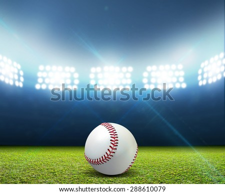 A stadium with an unmarked green grass pitch and a white baseball ball at night under illuminated floodlights - stock photo