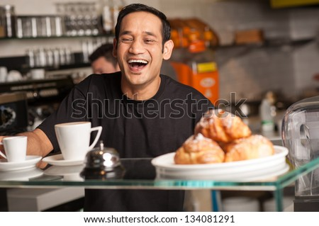 A staff at restaurant bursts out with laughter for a joke cracked by customer. - stock photo
