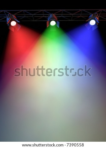 A Stage Light Rack with 3 RG&B Colored Spotlights Shining down towards the middle of the layout in a dark area. - stock photo
