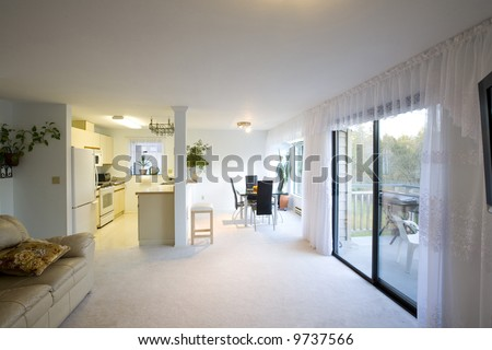 A staged dining room, kitchen, and living room in a condominium. - stock photo