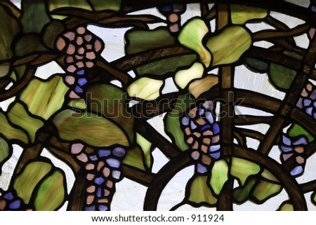 A stained glass panel with grapes on the vine. - stock photo