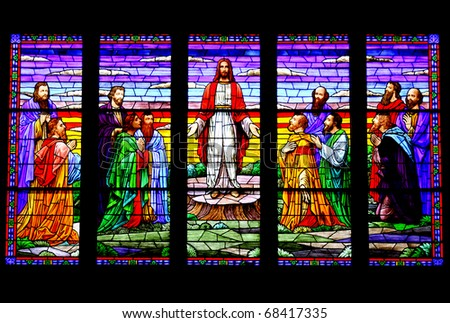 A stained glass window depicting Jesus and his followers. - stock photo