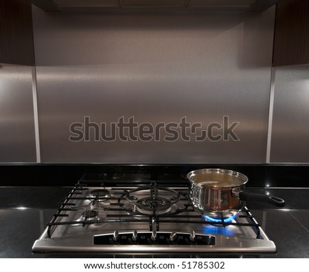 A stainless steel pan full of boiling water on a gas hob in a modern kitchen. - stock photo