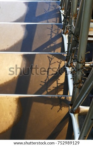a stairrail with barbwire sheds a shadow on steps of a metal staircase