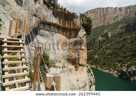 A stairs path encrusted in a rock over a river - stock photo