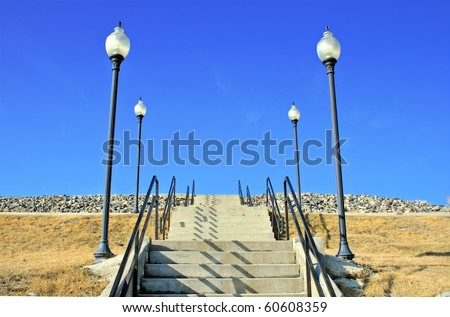 A stairway leading up to an unknown location with light poles on both sides. - stock photo