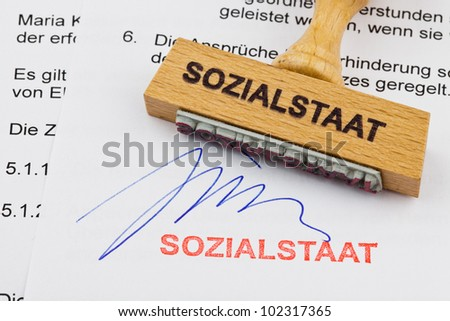 a stamp made of wood lying on a document. german words: welfare - stock photo