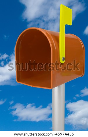 A standard orange mailbox and flag isolated over a blue sky - stock photo