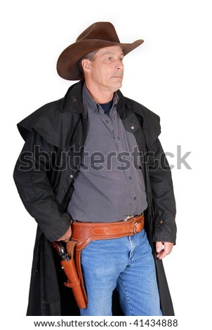 A standing cowboy with his hand on his gunbelt. - stock photo