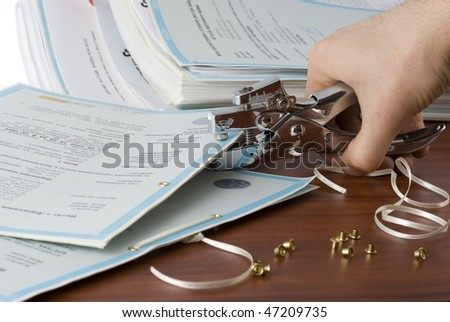 A stapler, accessories and documents on a wooden desk
