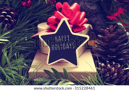a star-shaped chalkboard with the text happy holidays on a pile of gift boxes placed under the christmas tree and surrounded by natural ornaments such as pine cones - stock photo