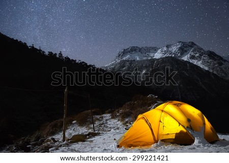 A starry night sky high in the mountains and a tent.  - stock photo