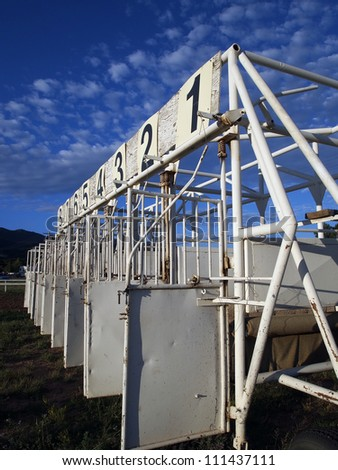 A starting gate for horse racing at a rural track. - stock photo