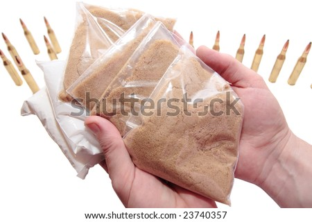 a stash of drugs bullets and money showing a dangerous cost to life against a white background - stock photo