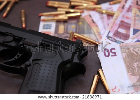 a stash of drugs gun and money showing a dangerous cost to life against a dark background - stock photo