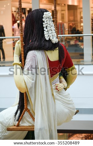 A statue/ mannequin of woman in Kerala sitting on a swing wearing traditional handmade white silk sari / saree with golden details, woman use to wear on Onam, Vishu festival Kerala India.