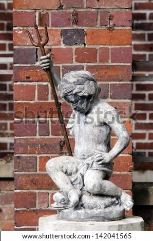 A statue of a baby poseidon. - stock photo