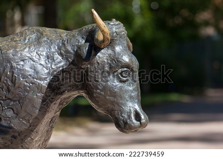 A statue of a bull or torus, in the afternoon sunshine with a blur background. - stock photo