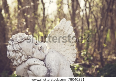 A statue of a small child with wings in the woods.