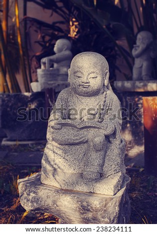 A statue of a sramanera holding a Buddha's teaching book, meditates on the words of Buddha in Buddhist temple. Sramanera is a novice monk holding the ten precepts. - stock photo