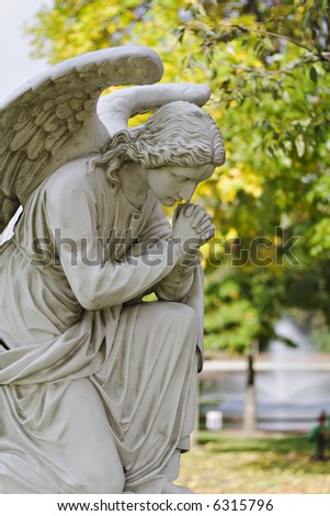 A statue of an angel in a garden praying. - stock photo