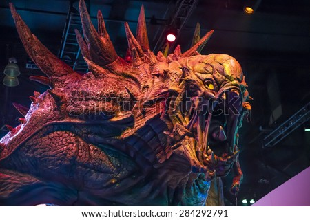 A statue of the Behemoth monster from the video game Evolve stands over the crowd at the E3 Electronic Entertainment Expo in Los Angeles, California, June 2014. - stock photo
