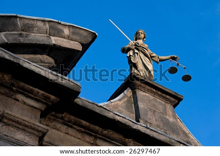 a statue of the goddess of justice atop a building - stock photo