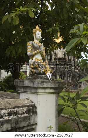 a statue outside a temple is in a prayer and showing respect position