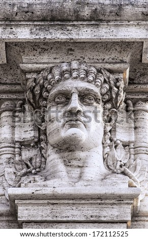 A statue relief of emperor Nero's head on the gateway entrance to the park that contains the ruins of his golden palace at domus aurea in Rome. - stock photo