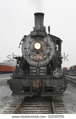 A steam engine heading straight towards the camera. - stock photo