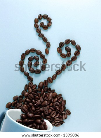 a steaming cup of coffee beans - stock photo