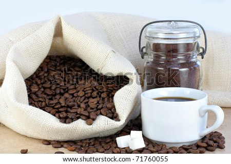 A steaming hot cup of coffee next to a burlap bag of coffee beans.  Sugar cubes and beans around cup. - stock photo