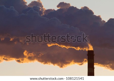 A steaming power plant pipe against sunset sky - stock photo