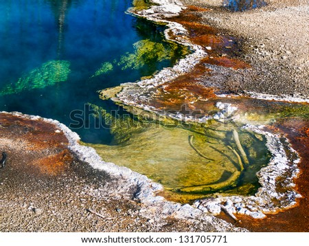 A steaming thermal hot spring pool in the West Thumb Geyser Basin of Yellowstone National Park displays fantastic colors. - stock photo