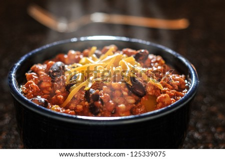A steamy bowl of Chili topped with cheddar cheese with a fork in the background - stock photo