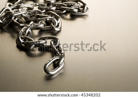 a steel chain on a metal background. First few links in focus - stock photo