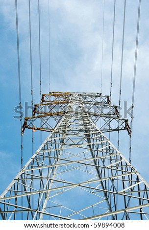 A steel electricity pylon against a blue sky - stock photo
