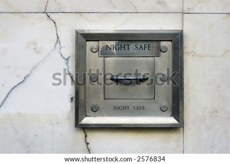 A steel night deposit box in the marble wall of a bank