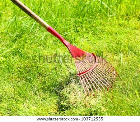 A steel rake on a grass. - stock photo
