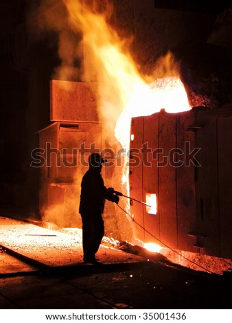 A steel worker takes a sample at steel company - stock photo