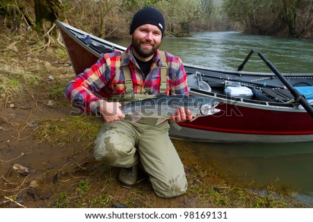 A steelhead fisherman holds his trophy fish by his boat and the river in Oregon. - stock photo
