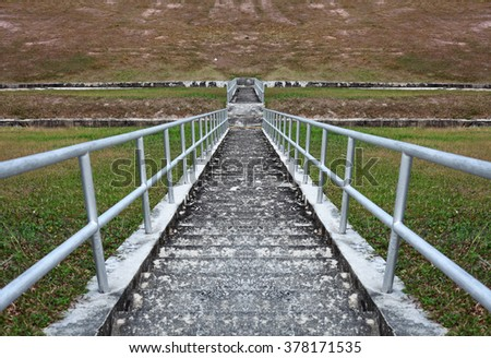 A steep concrete staircase going down a green grassy slope.  - stock photo