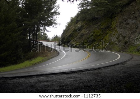 A steep corner on a wet winding road - stock photo