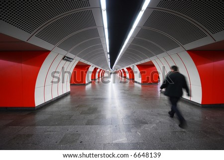 A step into the future - man waking in a futuristic tunnel - stock photo