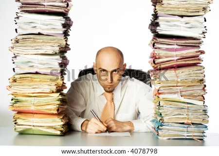 A stern and unpleasant administrative clerk glares through two huge stacks of business files, clearly indicating he has not time or desire to be of any customer service. - stock photo