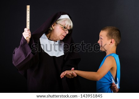 A stern nun holding a ruler in a threatening manner to a frightened boy.