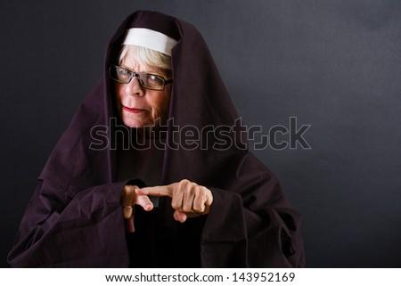 A stern nun tsk tsk with her finger. - stock photo