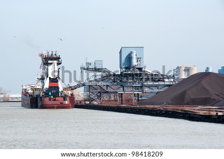 A stern view of an articulated tugboat and barge docked at the Cleveland Bulk Terminal in the Cleveland Harbor on Lake Erie,  The boat is taking on iron ore to be delivered to a steel mill - stock photo
