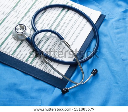 A stethoscope and RX prescription are lying on a medical uniform - stock photo