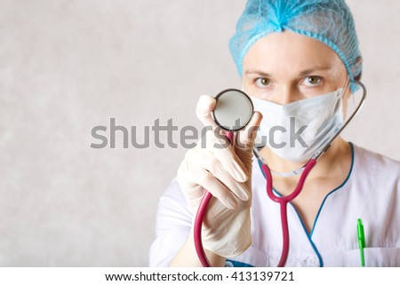 A stethoscope in the hand of a doctor dressed in a white professional uniform with clip cap and protective mask. White background.